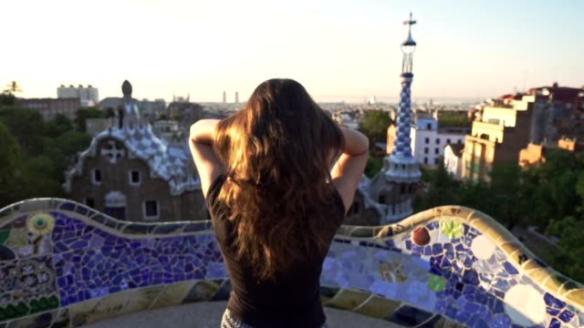 Beautiful girl combing hair with hand on Barcelona park. Enjoy Spain travel video