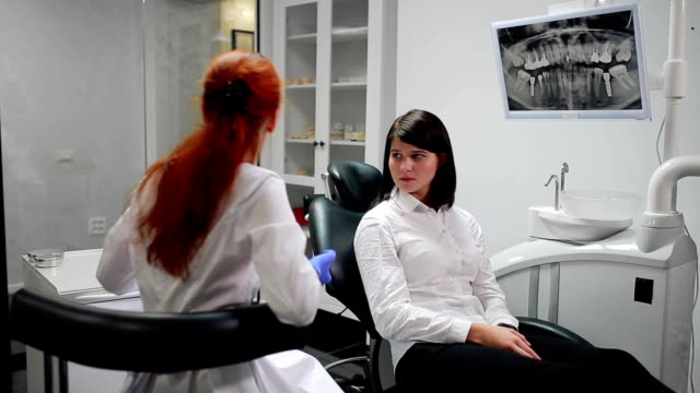 Beautiful girl consulted a dentist in his office ball on the thymus of the pain pointing to her teeth. White, sterile doctor's office. The screen shows an x-ray of the tooth in the oral cavity video