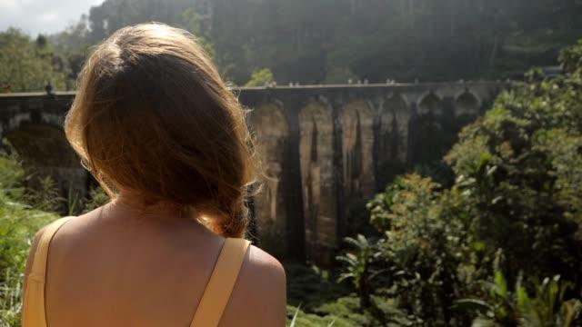 stockvideo's en b-roll-footage met mooi meisje dat oude treinbrug in de wildernis van sri lanka overweegt die dit verbazende land van azië onderzoekt en ontdekt. beroemde plaats bij negen boogbrug ella - camelia white