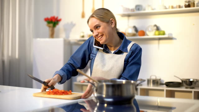 Beautiful girl cooking sauce while talking on phone, inviting friends for dinner