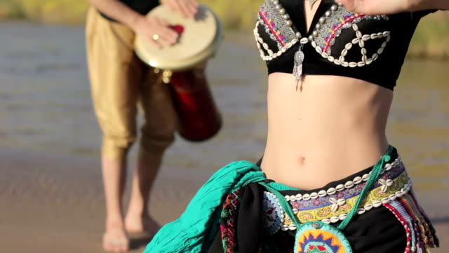 Beautiful  girl dancing exotic dance with drummer video