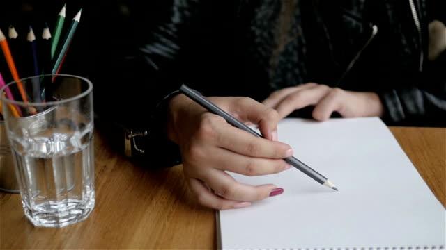 Linda garota elaboração com lápis, copo de água e lápis coloridos na mesa de madeira, simulado, janela grande - vídeo
