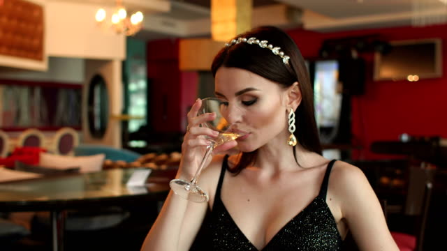 Beautiful girl drinking a Martini in a restaurant. video