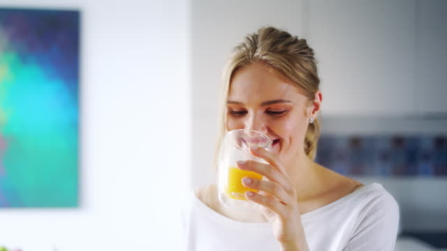 vídeos de stock e filmes b-roll de beautiful girl drinking fresh orange juice from glass. close up happy woman - sumo