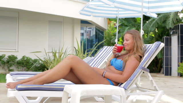 Beautiful girl drinking fruit juice while sitting by the pool Beautiful girl drinking fruit juice while sitting on a deck chair leotard stock videos & royalty-free footage
