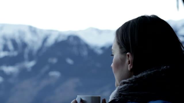 bella ragazza beve del tè caldo in montagna, primo piano - bevanda calda video stock e b–roll