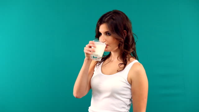 beautiful girl drinking yogurt milk from a glass on a green background video