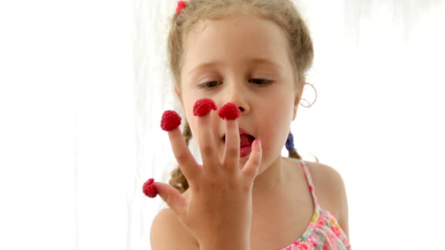 Beautiful girl eating raspberries on her fingers