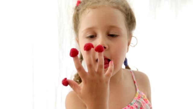 vídeos y material grabado en eventos de stock de hermosa chica comiendo frambuesas en sus dedos - frambuesa
