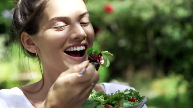 beautiful girl eating salad in the sunshine fo - healthy eating bildbanksvideor och videomaterial från bakom kulisserna