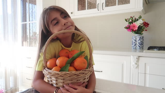 Beautiful girl eating tangerine to kitchen