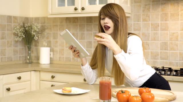 vídeos de stock, filmes e b-roll de linda garota come sanduíche e usa tablet na cozinha - comida feita em casa