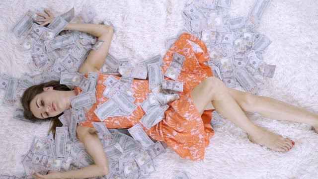 beautiful girl enjoys tremendous wealth. female lies on a white bed in a pile of dollar bills. Much money