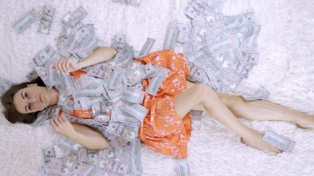 A beautiful girl enjoys tremendous wealth. the female lies on a white bed with a lot of money, in a pile of dollar bills