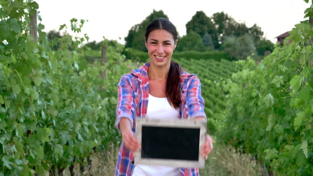 Beautiful girl (woman) farmer smiling watching the grape fields, holding a black board, in a shirt, wearing a straw hat. Concept ecology, wine bio product inspection water natural products agriculture video