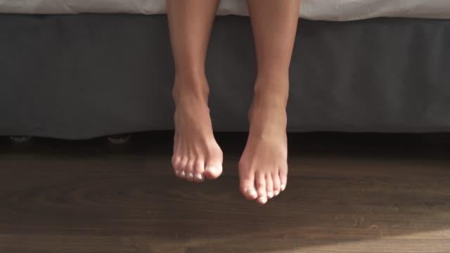 vídeos de stock, filmes e b-roll de pés bonitos da menina que penduram de um close-up da cama. - perna termo anatômico
