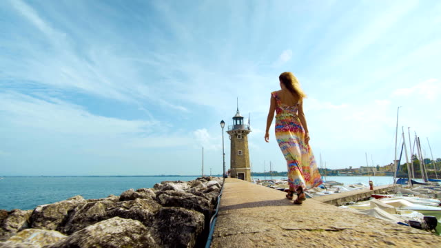 Beautiful girl goes to a lighthouse Beautiful girl goes to a lighthouse jetty stock videos & royalty-free footage