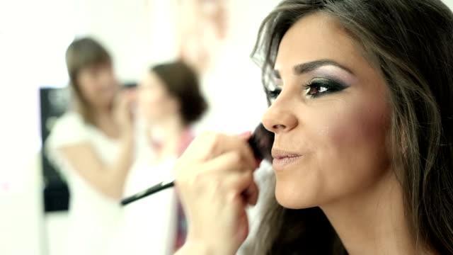 Beautiful girl having blusher applied video