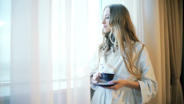 vidéos et rushes de belle jeune fille dans un peignoir boire du café - peignoir