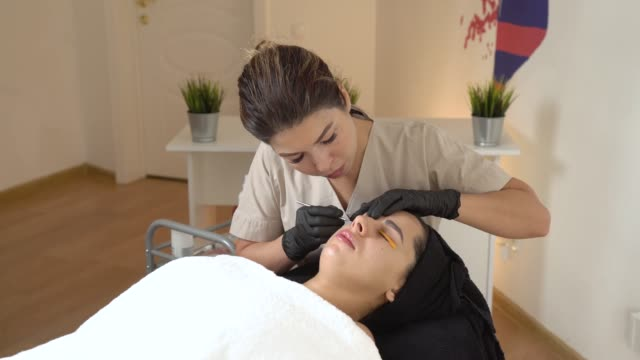 A Beautiful Girl in a Beauty Salon Does a Lamination Lashes. Beautician Performs the Procedure Eyelash Fragmentation. Beautician master A Beautiful Girl in a Beauty Salon Does a Lamination Lashes. Beautician Performs the Procedure Eyelash Fragmentation. Beautician master beautician stock videos & royalty-free footage