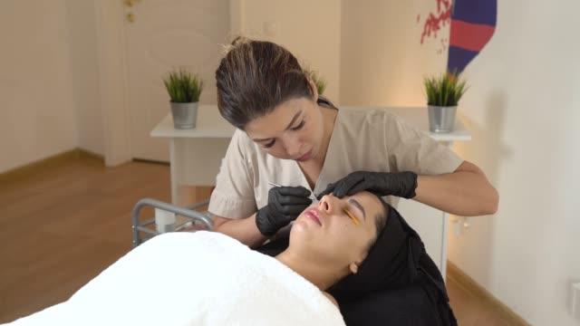 a beautiful girl in a beauty salon does a lamination lashes. beautician performs the procedure eyelash fragmentation. beautician master - kosmetyczka praca w salonie piękności filmów i materiałów b-roll