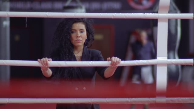 beautiful girl in a dark dress stand near the ring - sparring allenamento video stock e b–roll