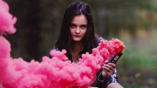 Beautiful girl in a forest waves around a color smoke grenade, slow motion video
