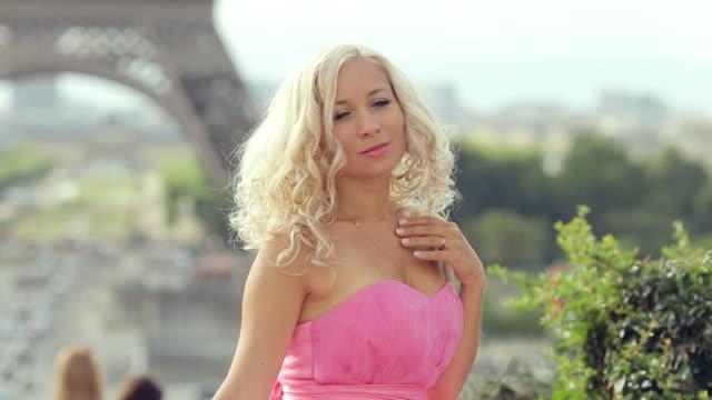 vídeos de stock, filmes e b-roll de linda garota em um vestido rosa festa sentado em um fundo da torre eiffel - moda parisiense