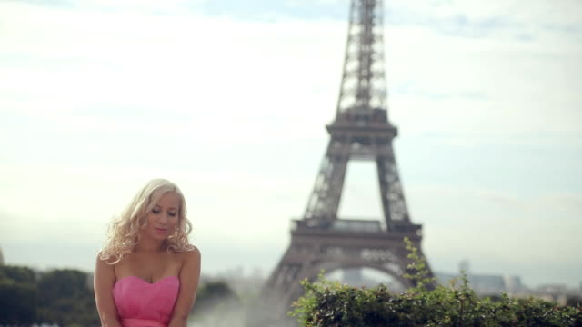 beautiful girl in a pink festive dress sitting on a background of the eiffel tower - paris fashion stock videos & royalty-free footage