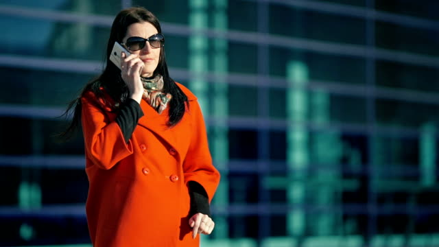 Beautiful girl in a red coat talking on the phone video