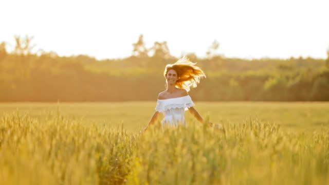 schönes mädchen in einem weißen kleid läuft über eine grüne wiese. junge hübsche frau geht in einem weizenfeld. - roggen stock-videos und b-roll-filmmaterial