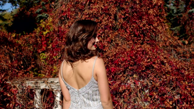 Beautiful girl in an evening dress walks in an old abandoned Park in the autumn