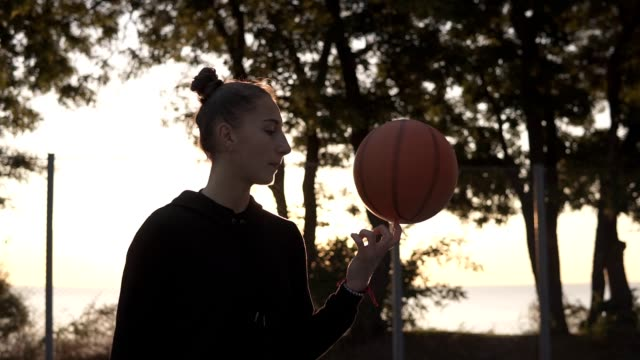 Beautiful girl in black hoodie spinning a basketball on her finger outdoors. Trees and sun shines on the background