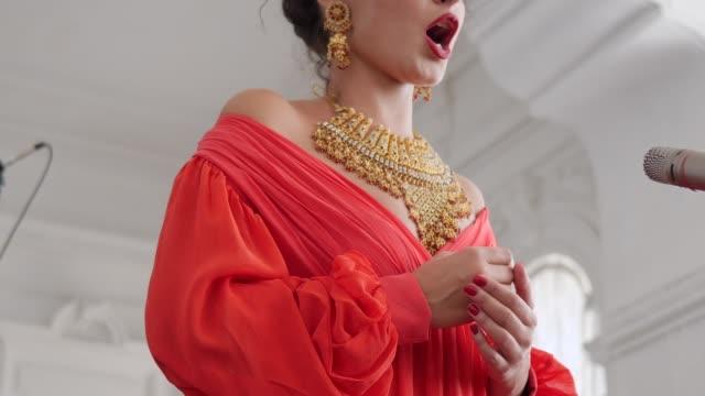 高価な宝石で美しい少女を感情的にシーンのマイクに向かって歌う - オペラ点の映像素材/bロール