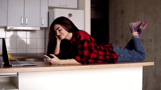 Beautiful girl in her 20's lying on her kitchen table surface an texting someone. video