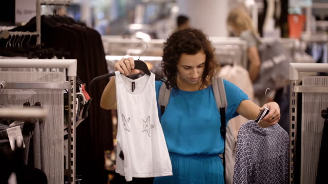 Beautiful girl in light blue dress is doing shopping and choosing between buying of white T-shirt or grey chemise. Young female consumer is making decision about purchasing in duty free shop video