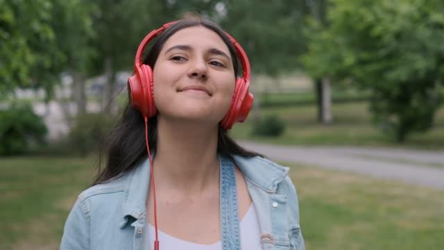 vacker flicka i röda hörlurar hoppar och lyssnar på musik - listen bildbanksvideor och videomaterial från bakom kulisserna