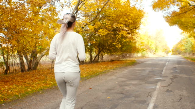 beautiful girl in sportswear engaged in sports outdoors, woman walks along the asphalt road and start running along autumn nature, concept healthy lifestyle and body care