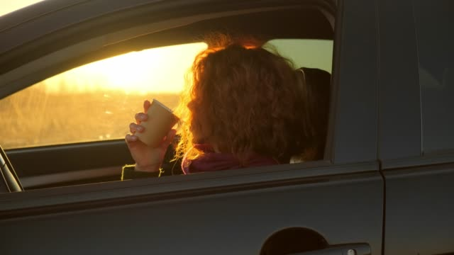 Beautiful girl in sun glasses is drinking coffee, looking at camera and smiling while sitting in her car video
