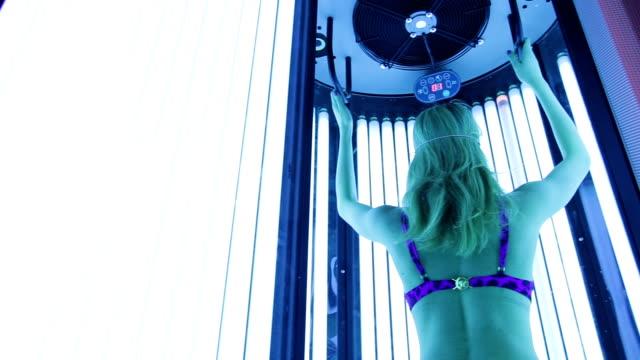 stockvideo's en b-roll-footage met mooi meisje in zwembroek op solarium - gebruind