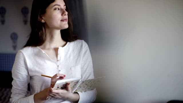 Beautiful girl in the morning writing notes in diary. She dreams and smiles video