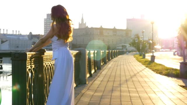 白い服の美しい少女は、市内の堤防に夜明けを満たしています。早朝、美しい一日。 ビデオ