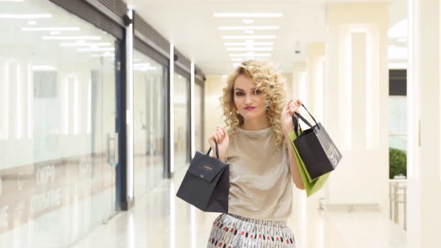 Beautiful girl is jumping with shopping bags in mall and smiling, happy with their purchases. slow motion. shopping, fashion, style and people concept