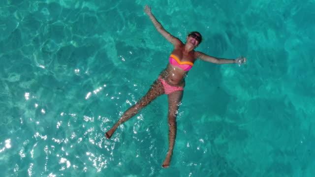 stockvideo's en b-roll-footage met mooi meisje legt in heldere blauwe water van de maldivische lagune - blond curly hair