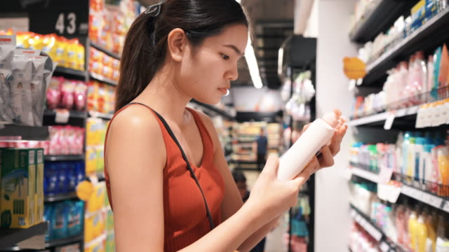 vídeos de stock e filmes b-roll de beautiful girl is shopping at the market mall. - protetor solar