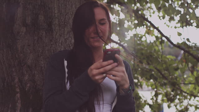 A beautiful girl leaning against a tree and using her phone and then smiling, slow motion A beautiful girl leaning against a tree and using her phone and then smiling, slow motion sweatshirt stock videos & royalty-free footage