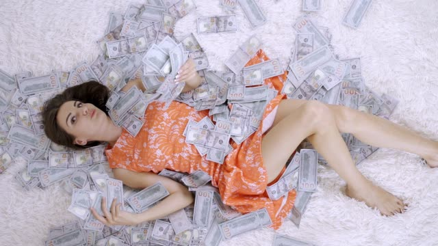 beautiful girl lies on a white bed in a pile of dollar bills. Tremendous wealth