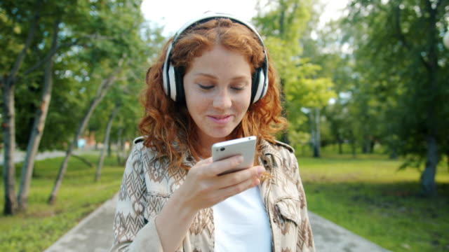 Beautiful girl listening to music in headphones using smartphone in green park Beautiful redhead girl is listening to music in headphones using smartphone smiling enjoying leisure time in green park alone. Modern devices and people concept. listening stock videos & royalty-free footage
