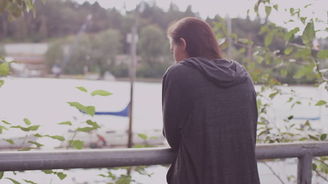 A beautiful girl looking out at a waterfront view, slow motion video
