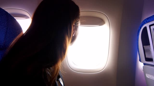 Beautiful girl looking out window of airplane during flight in slow motion